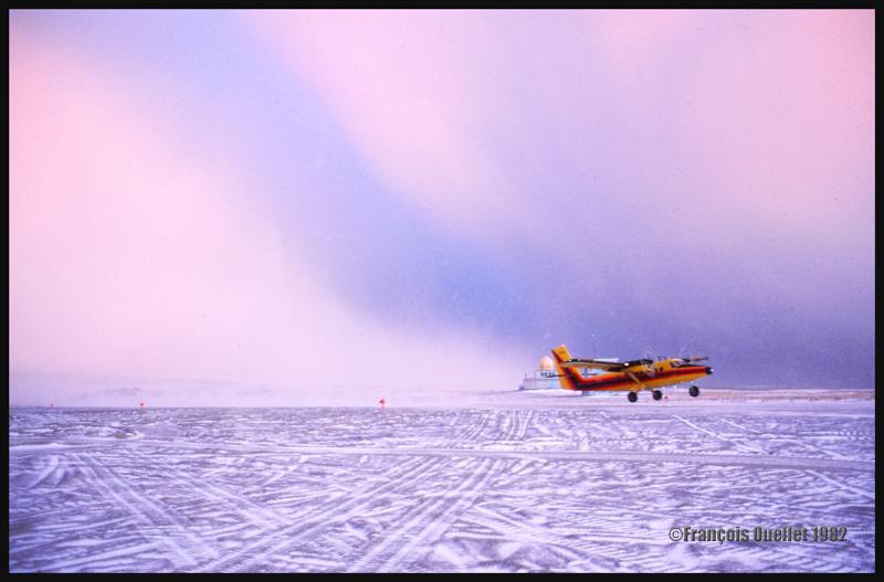 Décollage d'un Twin Otter d'Austin Airways durant une averse de neige à Inukjuak en 1982. En arrière-plan, le bâtiment d'aérologie d'Environnement Canada.
