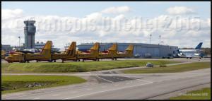 Tour de contrôle de Nav Canada avec, au premier plan, des CL-215 et Cl-415, un Challenger de Nav Canada et un Airbus d'Air Transat à l'aéroport international Jean-Lesage de Québec (CYQB).