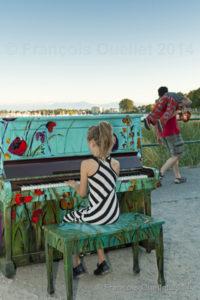 Une jeune fille joue du piano sur la plage de Willows Beach à Victoria.